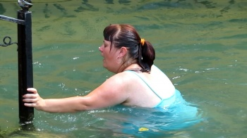 Big woman dipping into water
